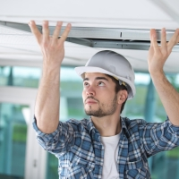 man_installing_tile_in_a_suspended_ceiling