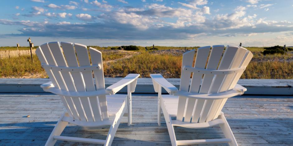 two_adirondack_chairs_overlooking_beach